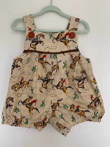 Cowboy print baby romper on coat hanger