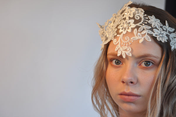 Girl looking at camera wearing white flowery headpiece