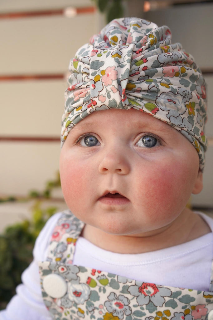 Baby wearing a liberty print turban looking at camera