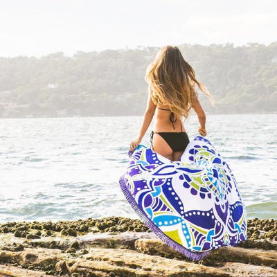 Asha Round Towel blowing in the sea breeze on the rocks