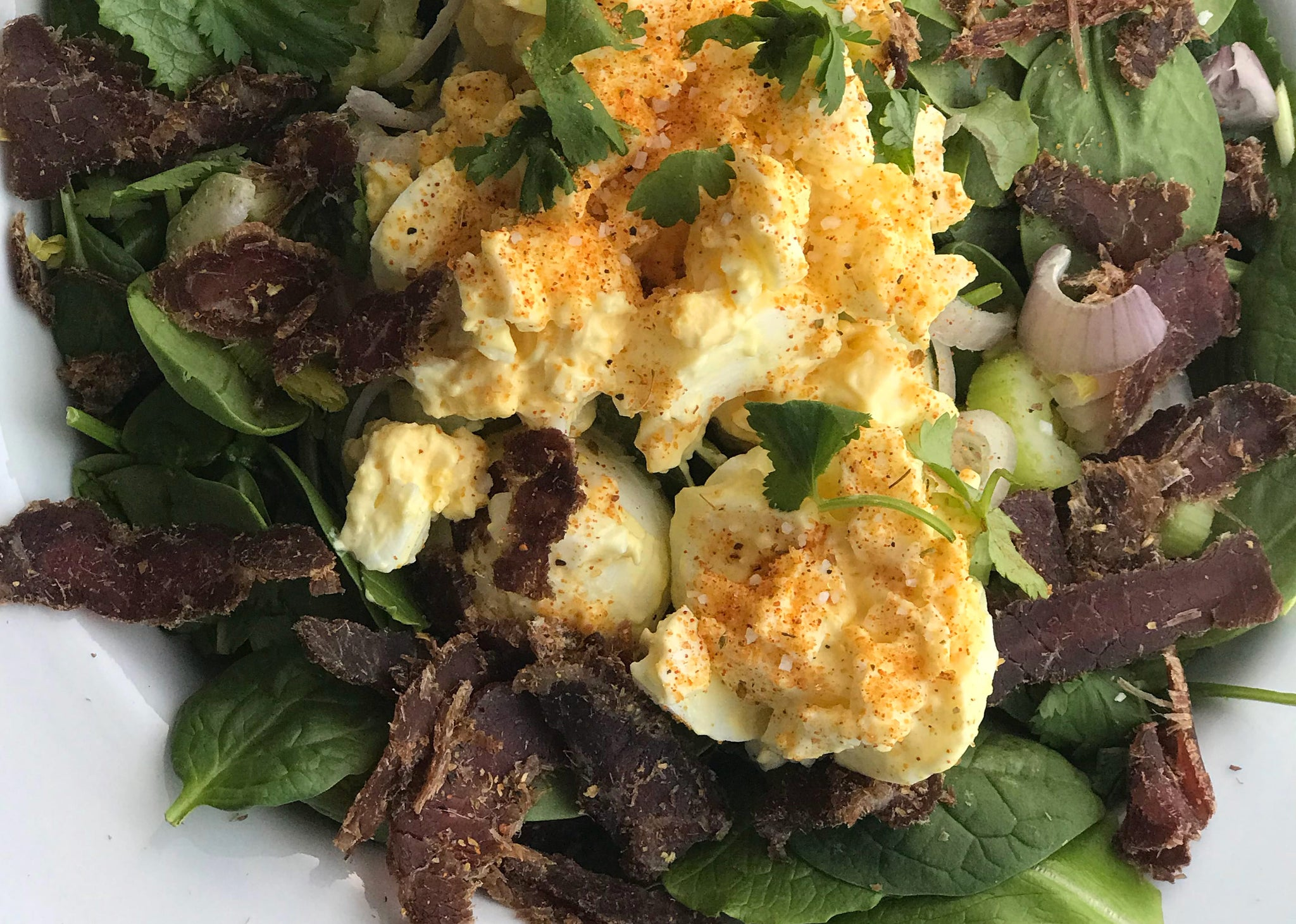 biltong salad with egg on white plate