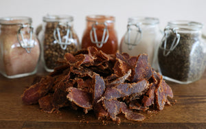 ayoba-yo biltong. grass fed and keto certified beef snack on wood table with natural seasonings.