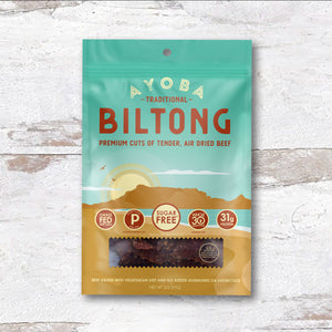 Ayoba Biltong Grass Fed Beef Snack Traditional Flavor. Paleo and Keto Certified Bag on Wood. 2 oz
