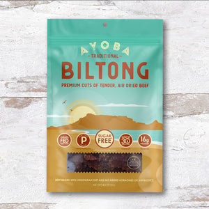 Ayoba Biltong Grass Fed Beef Snack Traditional Flavor. Paleo and Keto Certified Bag on Wood. 4 oz