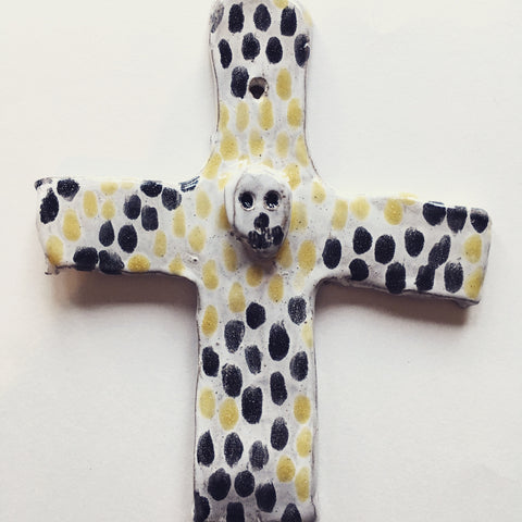 Playful painted ceramic cross with skull