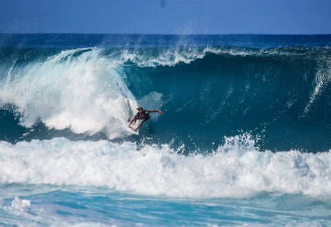 surfer-grabbing-rail-into-barrel-of-blue-overhead-wave-min