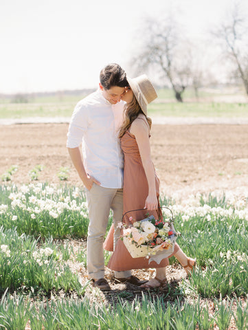 Couple kissing in a field of flowers with a spring bouquet in a basket and silk ribbon by The Lesser Bear Photo by Jenny Haas Florals Old Slate Farm Design and Planning Auburn and Ivory Creative
