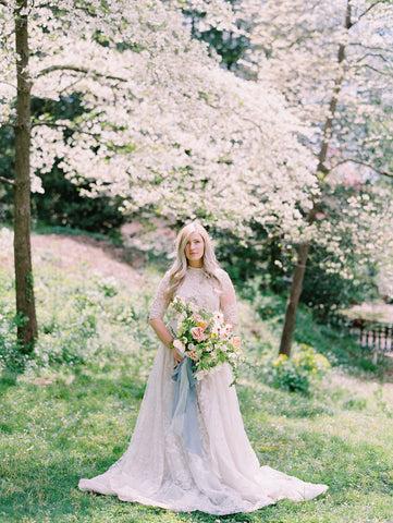 Bride under cherry blossoms holding bouquet with blue silk ribbon by The Lesser Bear Photography Jenny Haas Florals Passiflora Studios Design and Planning Auburn and Ivory Creative
