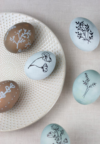 Grey and blue naturally dyed Easter eggs with white and black botanical illustrations by The Lesser Bear