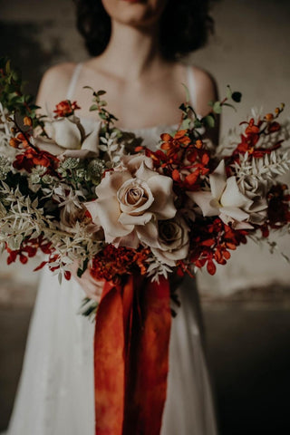 Bride holding bouquet with red silk ribbon photo by Grace E Jones Florals by Bear Roots