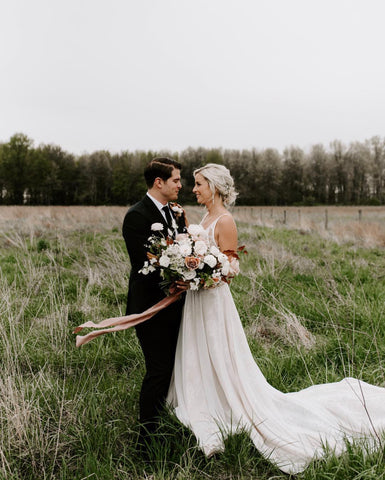 Married couple photographed in a field with bouquet and silk ribbon by The Lesser Bear