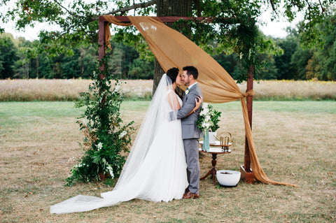 Naturally dyed silk gauze fabric in Pecan Brown, by The Lesser Bear draped over a wedding arbor