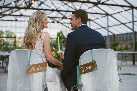 Bride and Groom Signs hanging on chair backs designed by Auburn and Ivory with silk ribbon by The Lesser Bear photo by Ashley West Photo