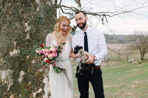 Bride and Groom Holding a Lamb and Bouquet with Naturally Dyed Silk Ribbon by The Lesser Bear Photo Tiernae Salley Florals Old Slate Farm