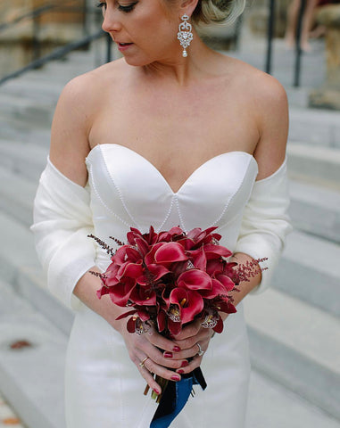 Bride holding cala lilies bouquet by Vessel Floral and Events with Navy Velvet Ribbon by The Lesser Bear STR Events and Photo by Kismet Visuals