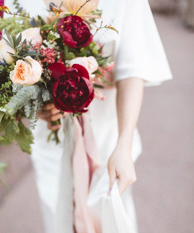 Bride holding red and pink bouquet with silk ribbon by The Lesser Bear Photo by Chad di Blasio
