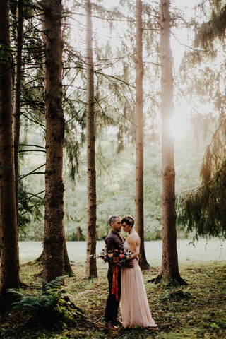 Bride and Groom in a grove of tall trees and moss. Photo by Addison Jones Florals by Bear Roots Floral and Custom Red Ribbon by The Lesser Bear