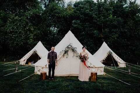 Bride and groom in front of three tents Photo by Addison Jones, Florals Bear Roots Floral and Custom Red Ribbon by The Lesser Bear