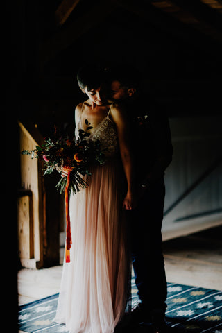 Bride and Groom in dramatic light inside barn photo by Addison Jones Florals by Bear Roots Floral and Red Ribbon by The Lesser Bear