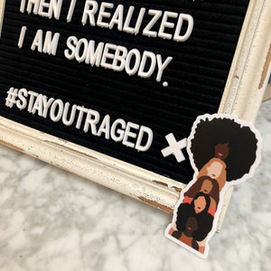 Photo of the sisterhood sticker next to a sign.