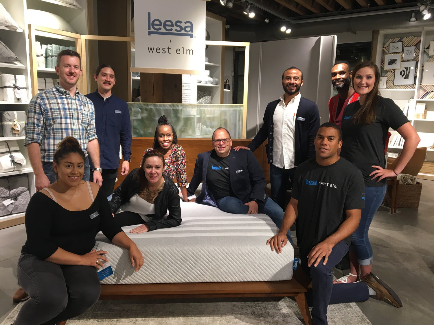 Leesa and West Elm team members kneeling around Leesa original mattress on display in a west elm store