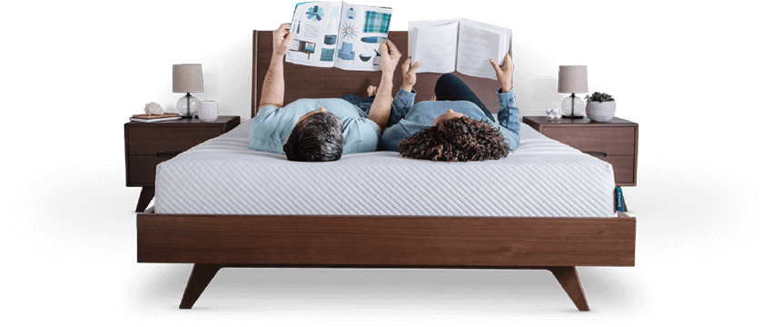 couple laying backwards on leesa original mattress while reading magazines and books