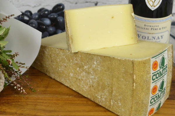 Comte AOP 18 months French Cheese on a cheeseboard. Wedge and bit