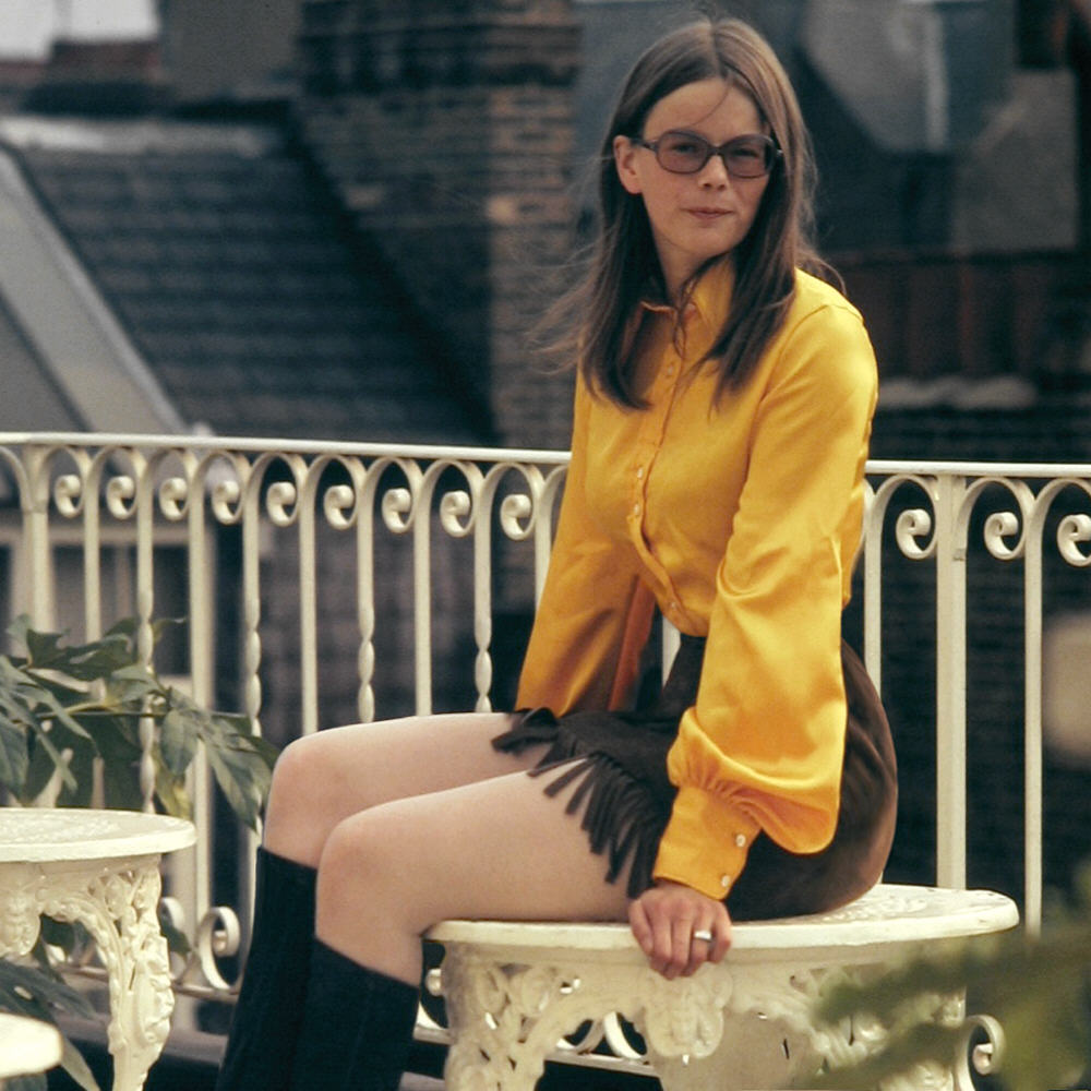 A girl in Kensington, London wearing a mini skirt, bell sleeves and 70's sunglasses
