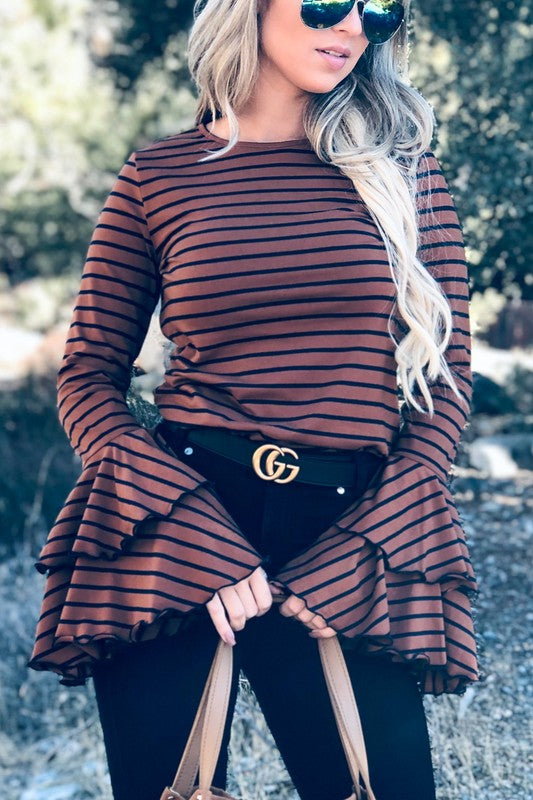 woman wearing brown and navy striped casual long sleeved with with double bell detail