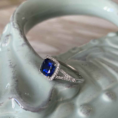 Women's blue sapphire & diamond halo engagement ring on blue tray