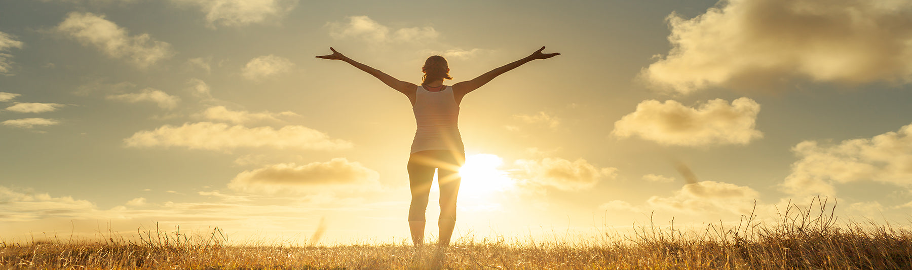 a photo of a woman facing the sun arms extended in gratitude