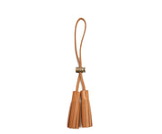 Tan Leather tassel keeper Add texture to your décor and get creative with the Cooper leather tassel keepers. Perfect for use as napkin holders, on curtains or doorknobs, as carry-on bag identifiers, and so much more. The Cooper leather tassel keepers are handcrafted with full-grain American leather.