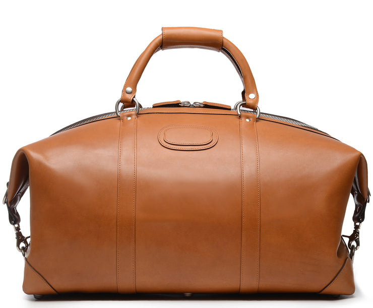"Tan 22"" Leather Weekender  The Twain weekender in Korchmar's Classic Leather is made of American cowhide leather that is selected from the top 5% of available hides. Colored only with aniline dyes, this leather retains its natural beauty over time and features visible markings that are characteristic of only the finest leather. One of our best-selling weekender styles, the Twain is ideal for leisure or business travel."