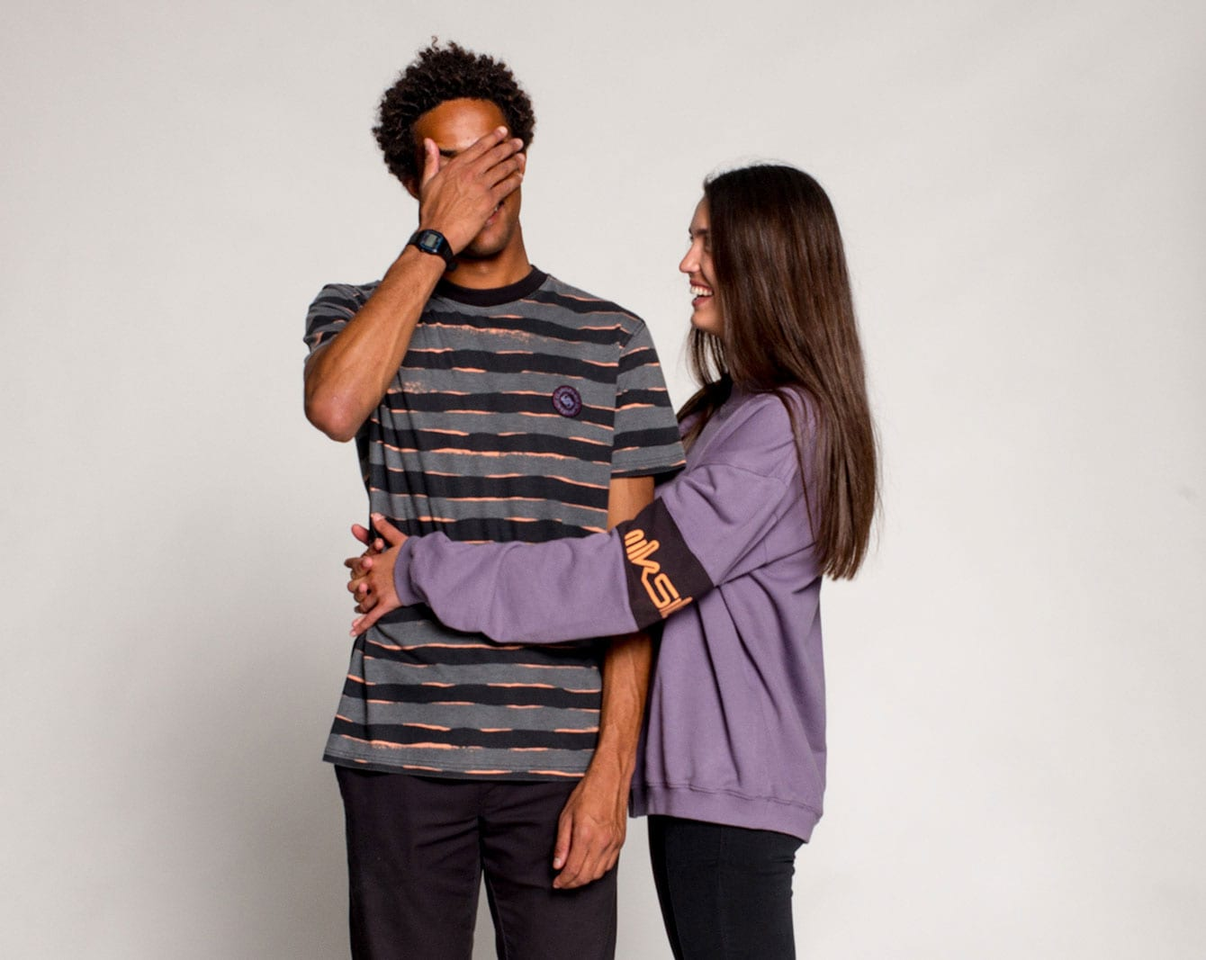 Man covering his face wearing a grey tshirt with black stripes hugged by girl wearing a purple sweater