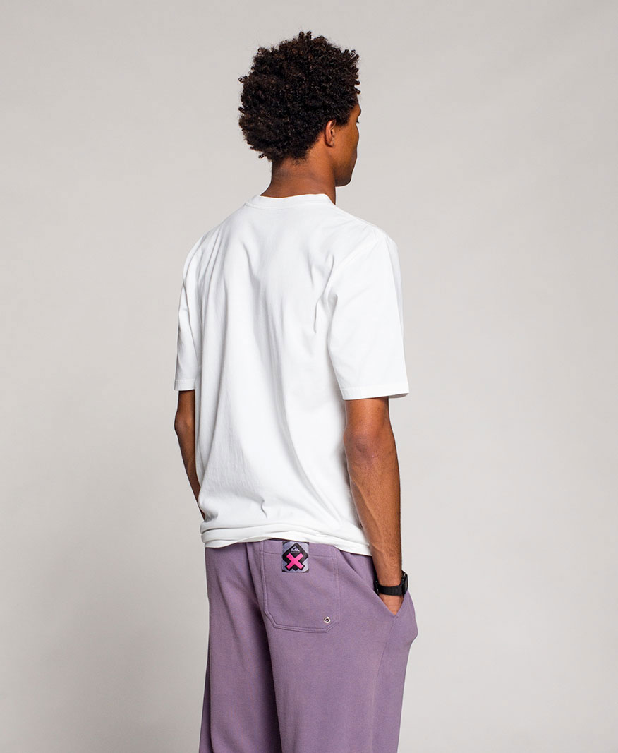 Man facing backwards wearing a white shirt with purple pants