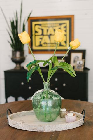 green vase with yellow tulips on wooden tray