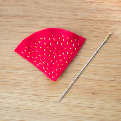 "Decorate the strawberry with tiny thread ""seeds"""