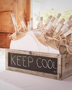 Rustic wooden box with chalkboard front with the words 'KEEP COOL'. Inside the box are hand crafted paper fans with rope around the handles, wrapped with lace fabric and finished off with a raffia ribbon bow.