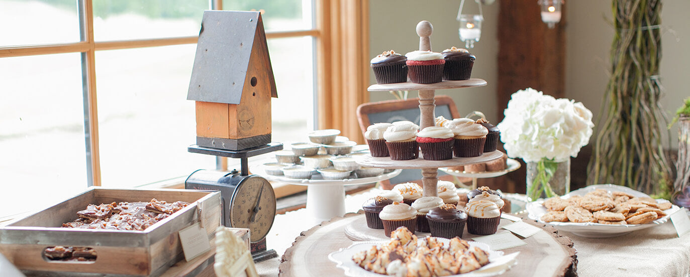 Rustic style wedding sweets table. Collection of cupcakes on a wooden cupcake stand, homemade baked goods. Featuring a vintage scale with a rustic birdhouse on top.