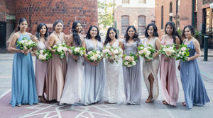 Photo of bride with all her bridesmaids in downtown Toronto. They are all holding neutral white themed bouquets.