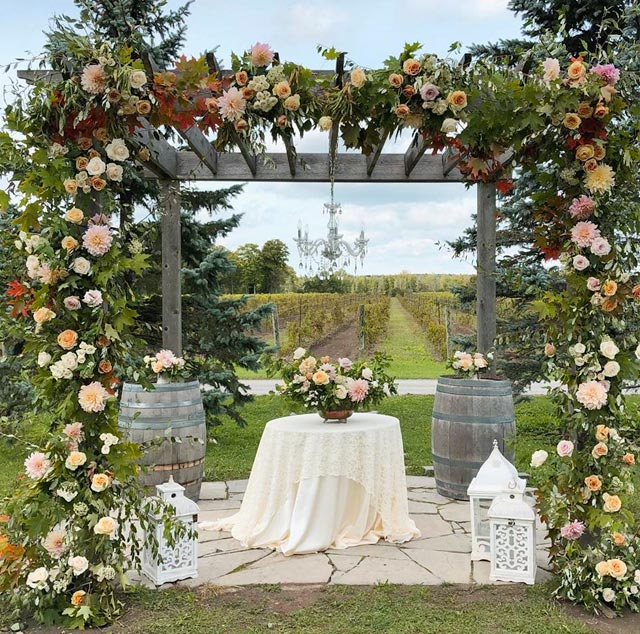 Beautiful arbour in a vineyard setting. The arbour is covered in flowers such as Cafe au Lait Dahlias. There are arrangements on top of two wine barrels. In the centre is beautiful centrepiece on cream linen round table with a classy chandelier. Beside the arbour are 3 large white lanterns.