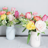Beautiful flower arrangement set in a pastel hand-painted mason jar.