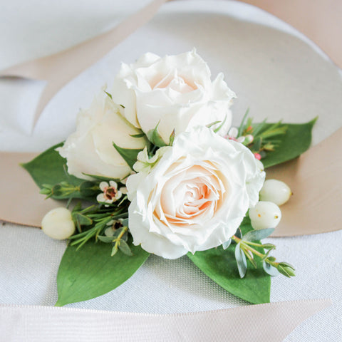 A delicate arrangement of white or ivory petite roses set on a premium ribbon, to be worn hand-tied as a wrist corsage.