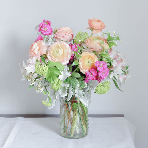 A tastefully-curated arrangement of fresh, seasonal flowers in a harmonious colour palette.  Set in a timeless hobnail jar.