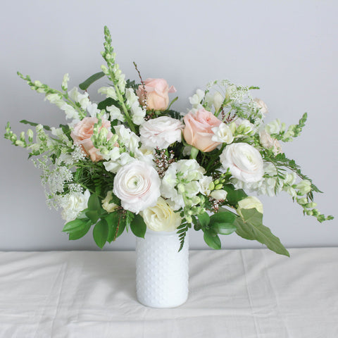 A tastefully-curated arrangement of fresh, seasonal flowers in a harmonious colour palette.  Set in a quaint milk-glass vase.