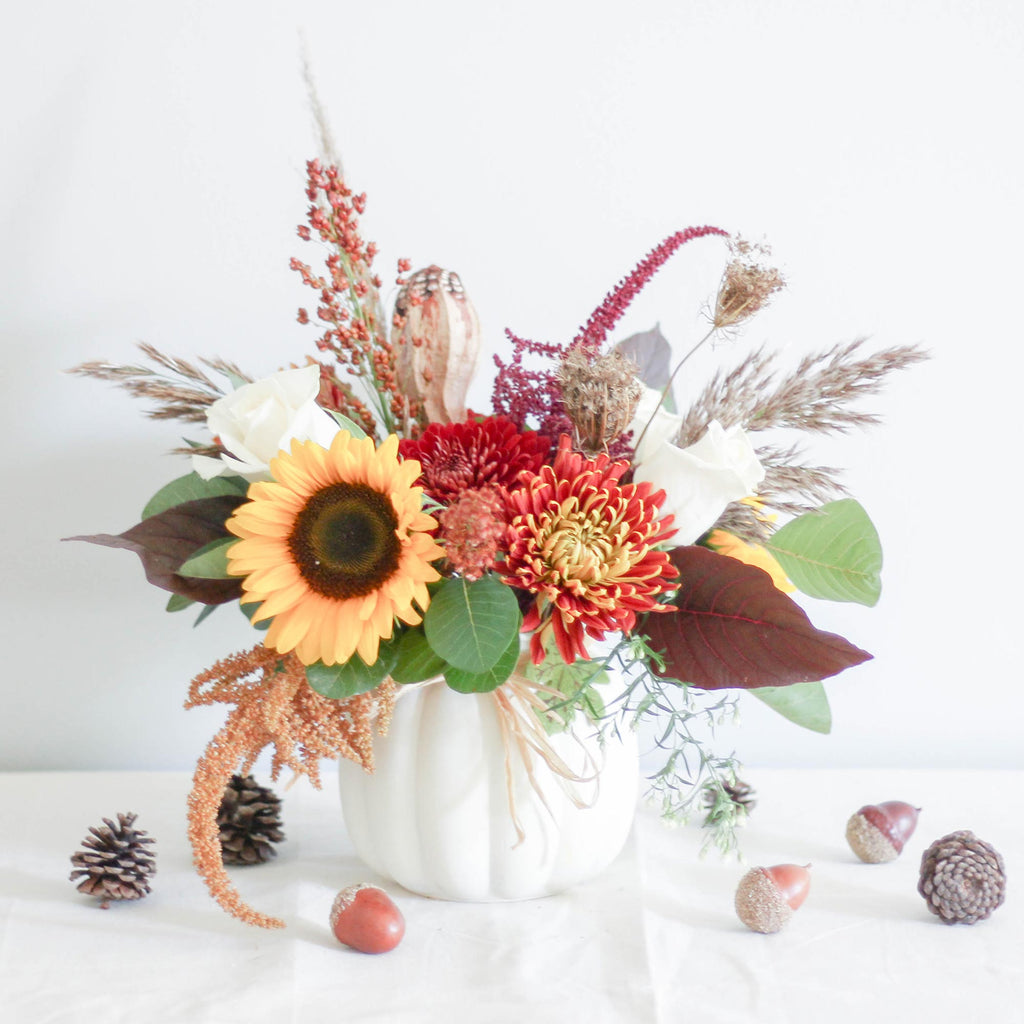 A tastefully-curated arrangement of fresh, seasonal flowers in a harmonious colour palette.  Set in a quaint glass pumpkin vase.