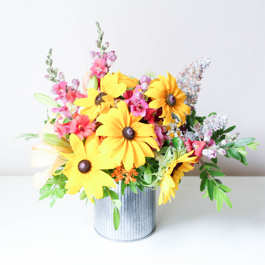 A tastefully-curated arrangement of fresh, seasonal flowers in a harmonious colour palette.