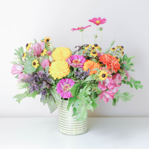A tastefully-curated arrangement of fresh, seasonal flowers in a harmonious colour palette.   Set in a charming rustic tin.