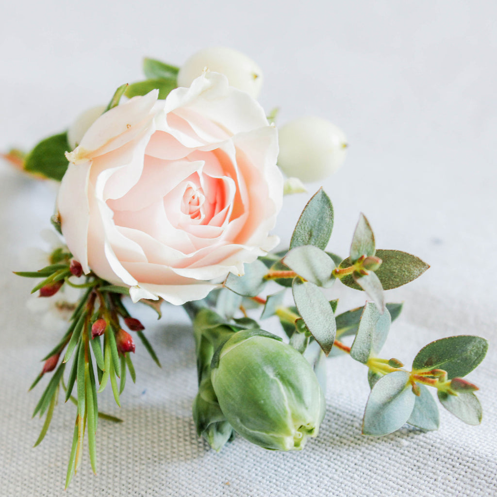 A single white or ivory petite rose, emphasized by its surrounding textural accents.