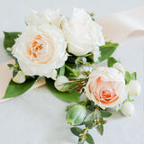 A coordinated pair of a hand-tied wrist corsage and a boutonniere. An exclusive value offering.